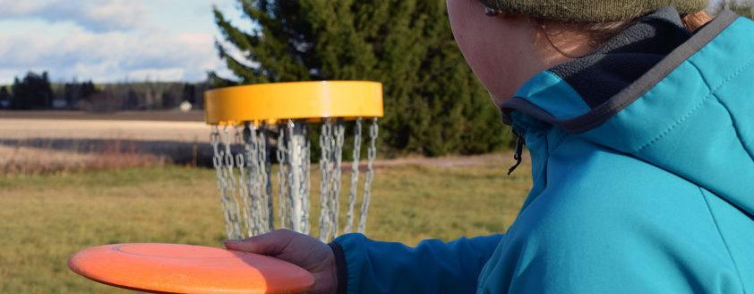 Mädchen wirft Disc Golf Richtung Korb
