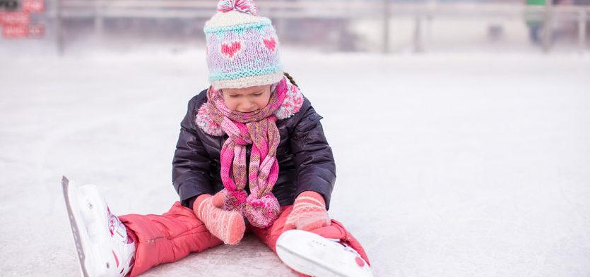 Kleines Mädchem mit Schlittschuhen auf dem Eis sitzend
