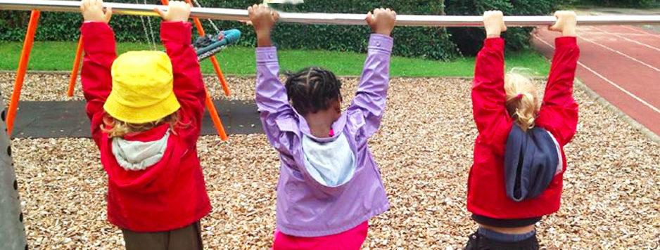 Kinder hängen an den Händen an Kletterstange