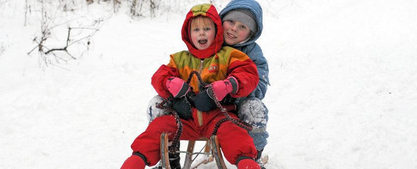 Zwei Kinder schlitteln