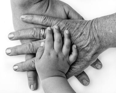 Hände dreier Generationen bereinander in schwarz weiss