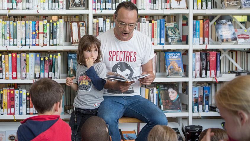 Dominic Deville liest am Schweizer Vorlesetag mit seinerTochter in der PBZ Bibliothek Hardau in Zürich © Désriée Good und SIKJM
